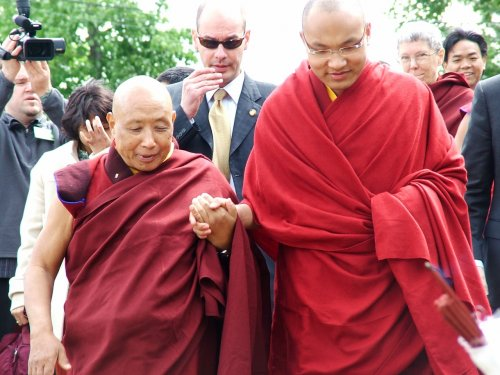 His Holiness walks with Lama Norlha Rinpoche.